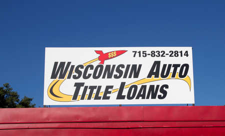 RIVER FALLS,WISCONSIN-NOVEMBER 12,2015: A Wisconsin Auto title loans sign against a blue sky.