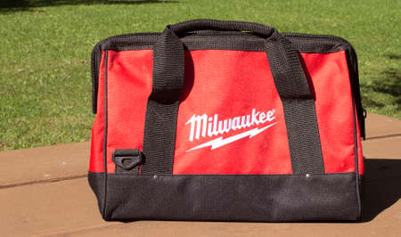 tool bag: RIVER FALLS,WISCONSIN-NOVEMBER 12,2015: A Milwaukee brand tool bag sitting on a wooden bench. Editorial