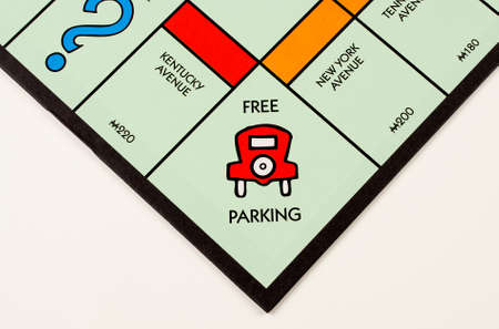 board: RIVER FALLS,WISCONSIN-NOVEMBER 16,2015: A Monopoly board featuring the Free Parking square. Monopoly originated in the United States in Nineteen Hundred and Three.