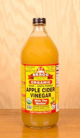 River Falls, Wisconsin-september 18,2016: Een fles Bragg merk appelazijn met een houten achtergrond.