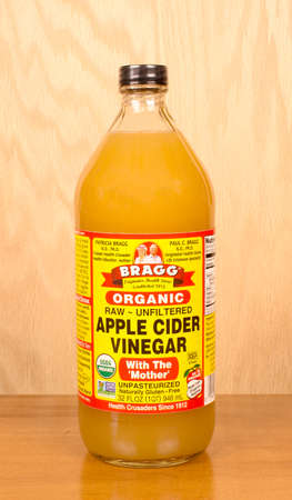 RIVER FALLS,WISCONSIN-SEPTEMBER 18,2016: A bottle of Bragg brand apple cider vinegar with a wood background.