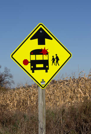 flashing: A sign indicating that you must stop for a school bus when the lights are flashing. Stock Photo