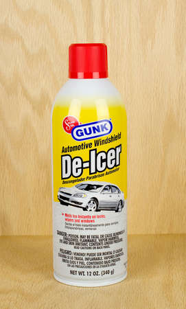 gunk: RIVER FALLS,WISCONSIN-MARCH 11,2017: A can of Gunk brand automotive windshield de-icer with a wood background.