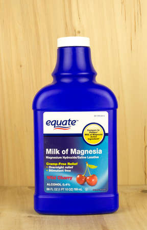 equate: RIVER FALLS,WISCONSIN-MAY 10,2017: A bottle of Equate brand Milk of Magnesia with a wood background.