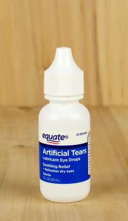 equate: RIVER FALLS,WISCONSIN-MAY 12,2017: A bottle of Equate brand artificial tears eye drops with a wood background. Editorial