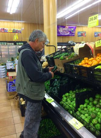 RIVER FALLS,WISCONSIN-OCTOBER 29,2017: A mature man shopping for peppers at the local grocery store. Redakční