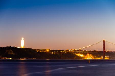 rei: The Christ the King statue (Portuguese: Cristo Rei) and partial view of the 25 de Abril Bridge (Ponte 25 de Abril) in Lisbon at sunset. Stock Photo