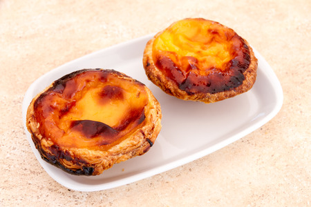 nata: Pastel de nata is a Portuguese egg tart pastry, common in Portugal, the Lusosphere countries and regions. They were mentioned by The Guardian as the 15th most tasty delicacy in the world Stock Photo