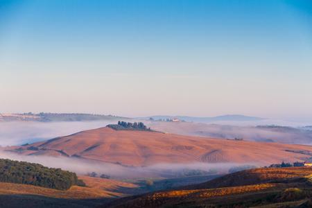 Crete Senesi landscape in Tuscany, Italy on a foggy summer dawn Stock Photo