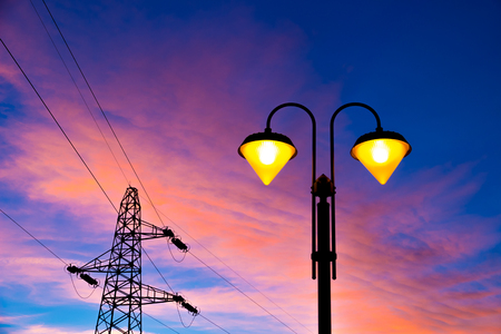 lit on streetlamp at sunset with high-tension line and pylon on the background