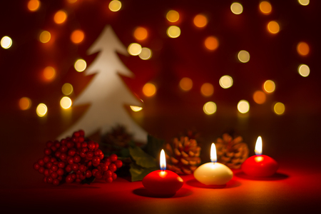 Christmas candles and ornaments over red dark background with lights