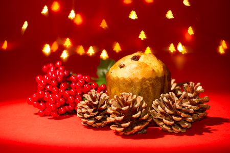 Delicious small Panettone and decorations with blurred christmas lights