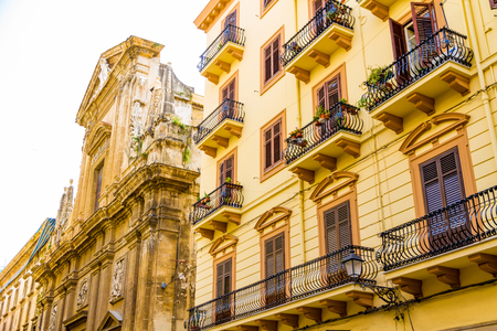 Church and building with balconies in old town center of Palermo, Italy