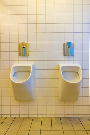 A urinal is a sanitary plumbing fixture for urination only. Stock Photo