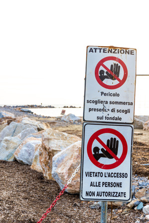 Warning signs reading: Warning. Danger submerged reef, rocks on the shoal are present and no entry unauthorised personnel near a construction site on the shoreline in Follonica, Italy Stockfoto