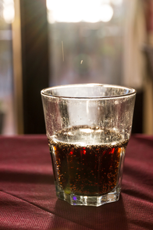 A beautifully backlit glass of red soft drink on a restaurant table in Italy at sunset