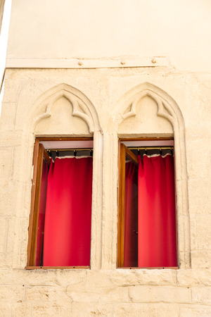 Montpellier, France. Two windows with decorations and red curtains in the old town