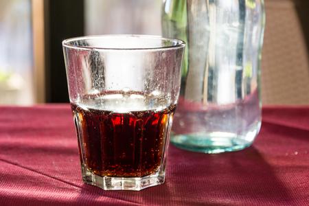 Un vaso de refresco rojo bellamente retroiluminado en una mesa de restaurante en Italia al atardecer Foto de archivo