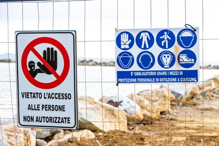 Warning signs reading: 'no entry unauthorised personnel' and 'protective equipment must be worn' near a construction site on the shoreline in Follonica, Italy