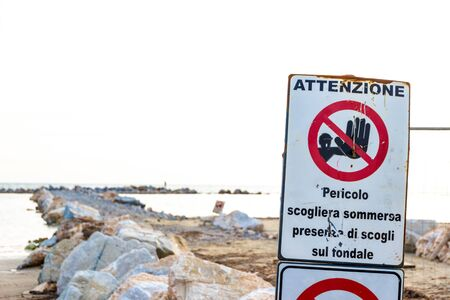 Warning signs reading: 'Warning. Danger submerged reef, rocks on the shoal are present' near a construction site on the shoreline in Follonica, Italy Reklamní fotografie