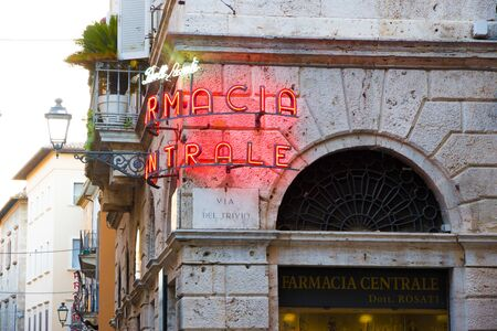Ascoli Piceno, Italy - June 27, 2019: glowing neon sign in the old town readings: Doctor Rosati Central pharmacy at sunset