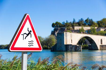Fall hazard sign with The Pont Saint Benezet or Avignon bridge in the background