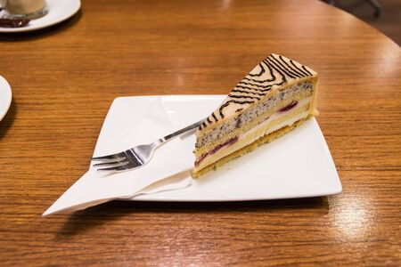 Slice of marzipan cake with tray and fork served in a classy coffee bar in Vienna, Austria