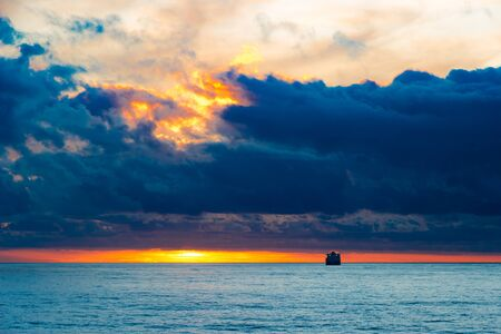 Sea sunset landscape with cloud  sun reflection and ship on the horizon