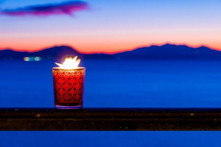 Beautiful candle glass at sunset in Italy with sea and Elba island in the background Stock fotó