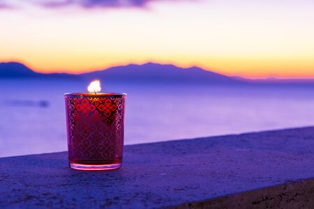 Beautiful candle glass at sunset in Italy with sea and Elba island in the background 免版税图像