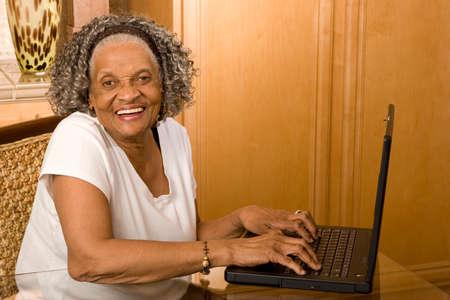高齢者アフリカ系アメリカ人女性のコンピューターで作業します。 写真素材