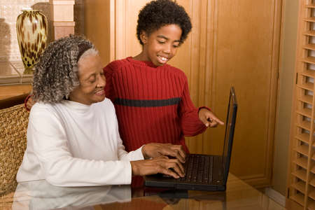 Happy eldely woman and her grandson on the computer.