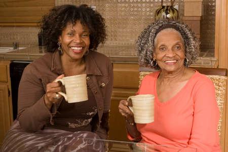アフリカ系アメリカ人の母は彼女の娘と一緒にコーヒーを飲んでいます。 写真素材