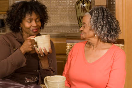 African American mother having coffee with her daughter. Imagens