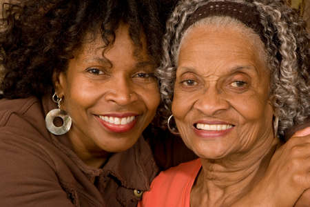 her: Mature African American mother hugging her daughter.