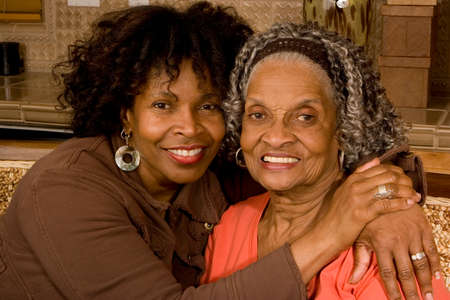 Mature African American mother hugging her daughter.