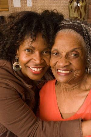 성숙한 아프리카 계 미국인 딸이 그녀의 어머니를 포옹입니다. 스톡 콘텐츠