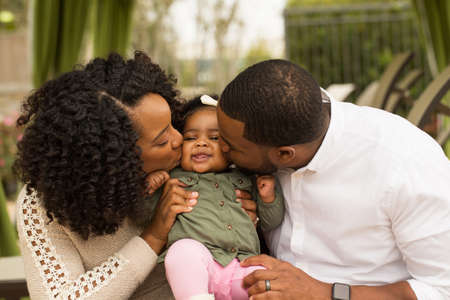 padres hablando con hijos: Feliz familia afroamericana con su bebé.
