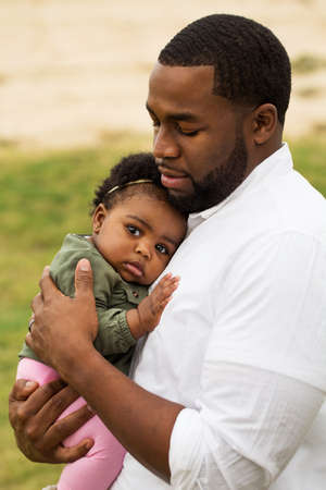 African American father holding his daughter.