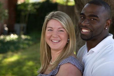 幸せな多文化のカップルを抱いて、笑顔を愛するします。