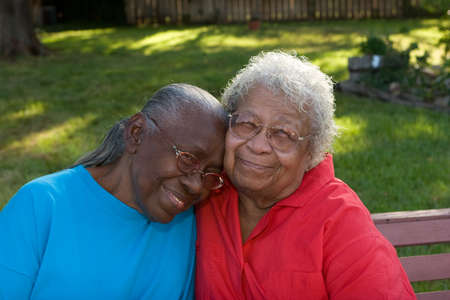 Gelukkig volwassen Afro-Amerikaanse zussen lachen en glimlachen.