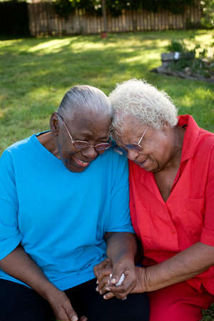 Happy mature African American sisters laughing and smiling.