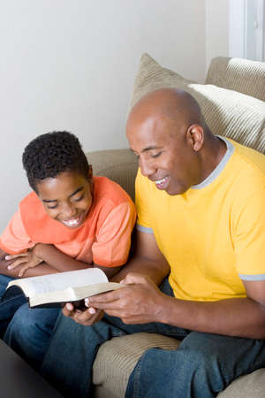 African American man reading with his son.