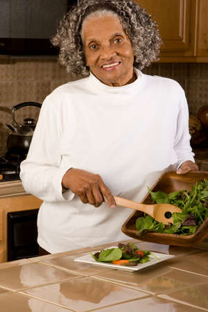 vegtables: Portrait of an elderly African American woman at home.