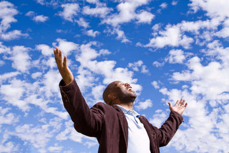 african worship: African American man standing outside with open arms. Stock Photo