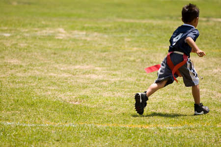 asian boy: Little boy kid playing flag football on an open field.