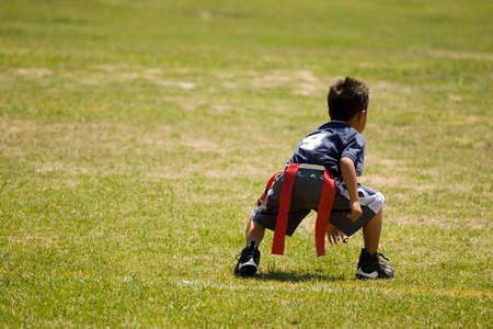 Niño pequeño niño jugando fútbol americano en un campo abierto.