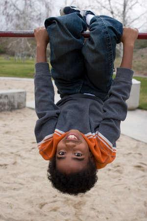 African American little boy on a slide.