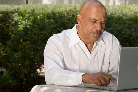 ラップトップ コンピューターに取り組んでいるアフリカ系アメリカ人の高齢者 写真素材