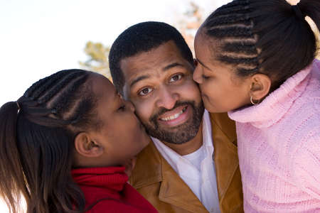 s day: African American father and his young daughters.
